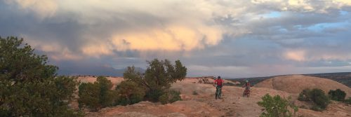 Storms abate after passing over riders on Rocky Tops section of Navajo Rocks, guided mountain bike tour, Moab UT