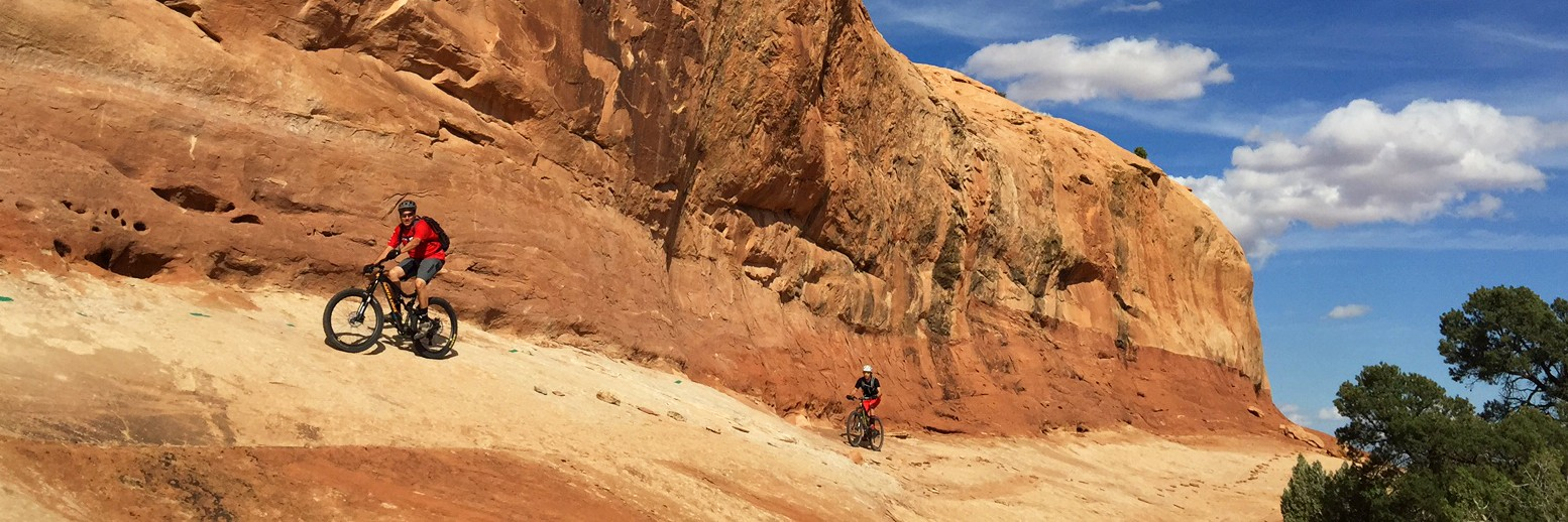 Two mountain bikers traverse a steep off-chamber section on Rocky Tops during a half-day guided tour of Navajo Rocks