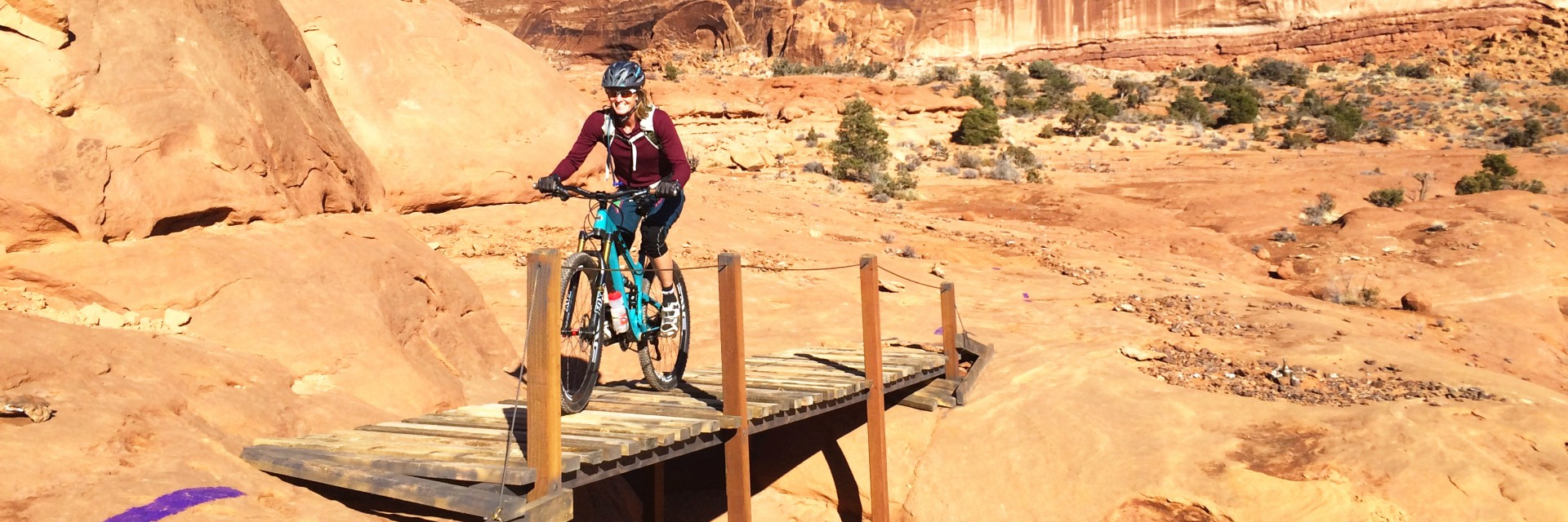 The Big Mesa section of the Navajo Rocks Trail includes a few wooden bridges across shallow ravines, as this mountain biker discovers on a guided half-day tour near Moab, UT