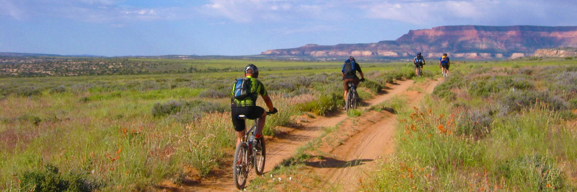 Mountain bikers head toward Indian Creek on the Lockhart Basin Road during a guided Needles to Moab tour