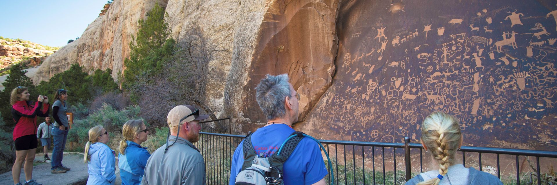 A group of mountain bikers takes in the Newspaper Rock ancient Indian rock art panel on day one of The Needles to Moab guided tour