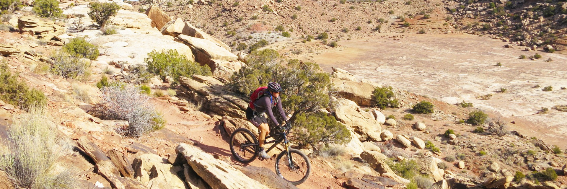 A rider descends the Alaska section of the North Klondike Singletrack guided mountain bike tour near Moab, UT