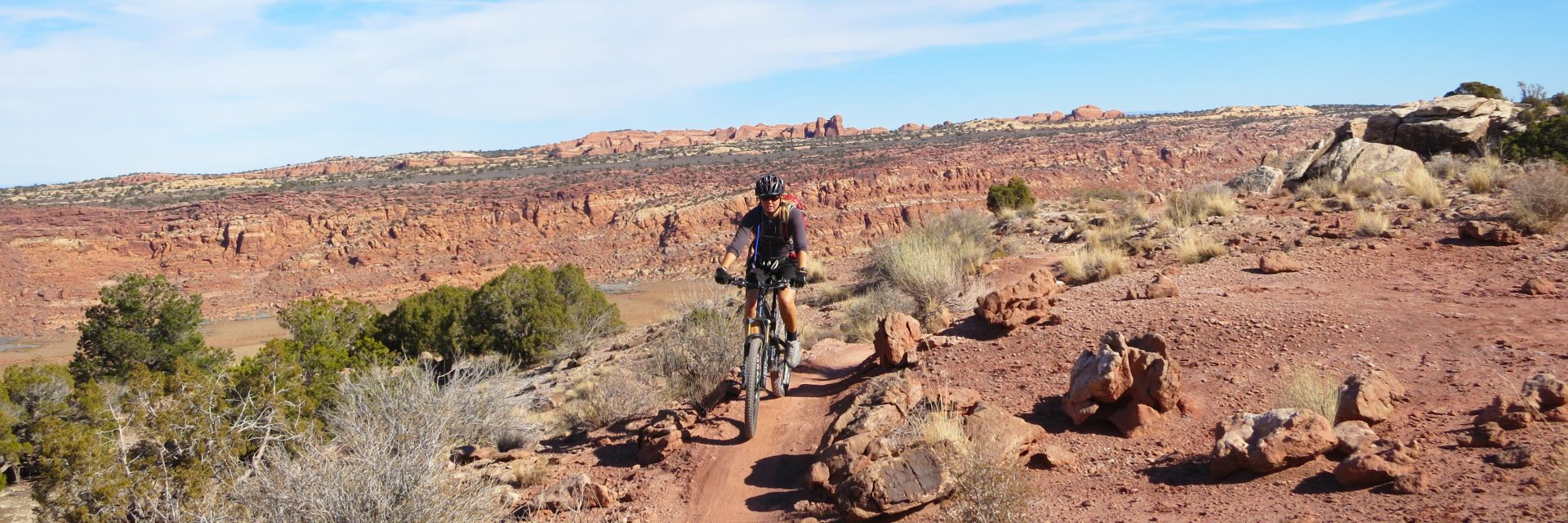 A mountain bike rider rolls along the top of the ridge on the Alaska section of North Klondike Singletrack above the Salt Valley and Arches National Park in the distance