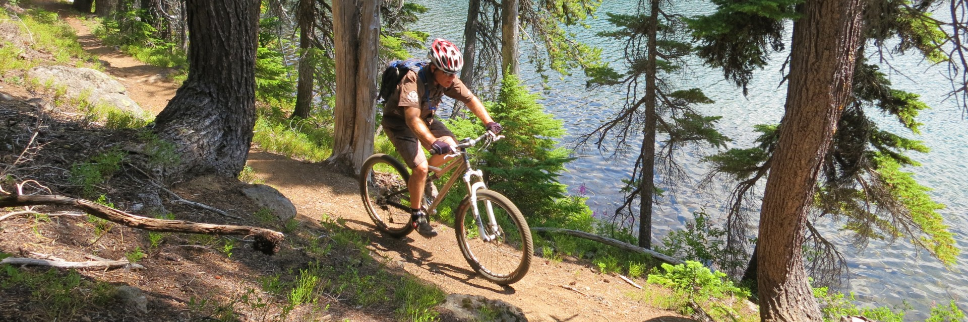 A biker leaves camp near a lake on the Oregon Cascade Singletrack guided multi-day tour west of Bend OR