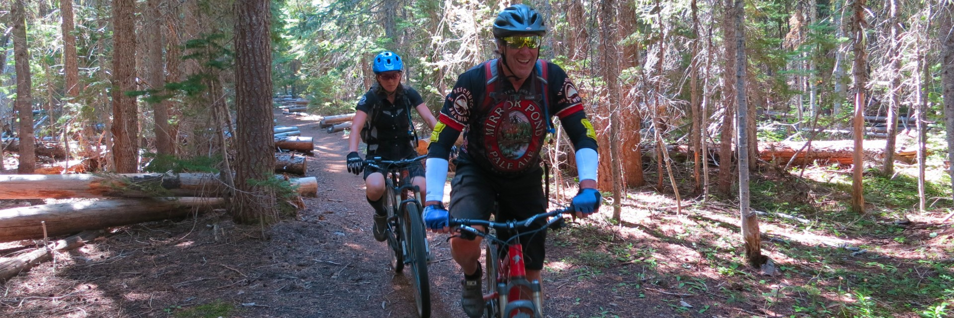 Mountain bikers negotiate the many log cuts encountered along the Oregon Cascade Singletrack guided tour near Bend OR