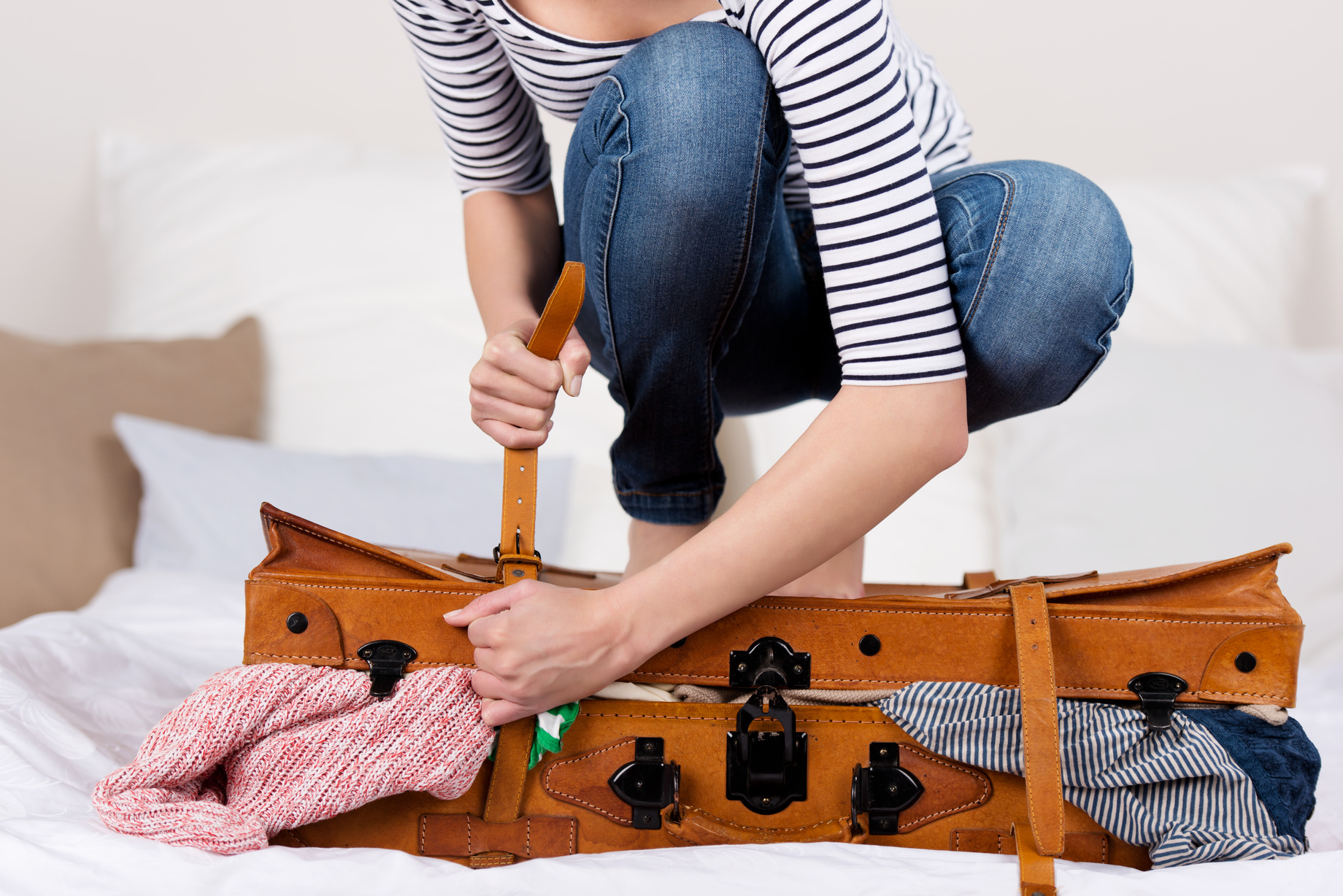 Midsection of young woman packing suitcase on bed illustrates what to do and what not to do when packing for your Rim Tours trip