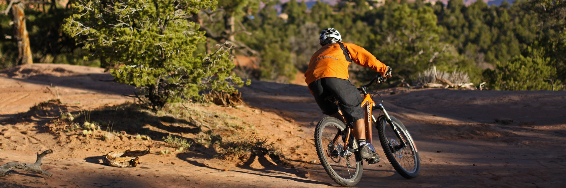 A downhill specialist carves a fast turn on the Upper Porcupine Singletrack section of The Whole Enchilada guided tour east of Moab, UT