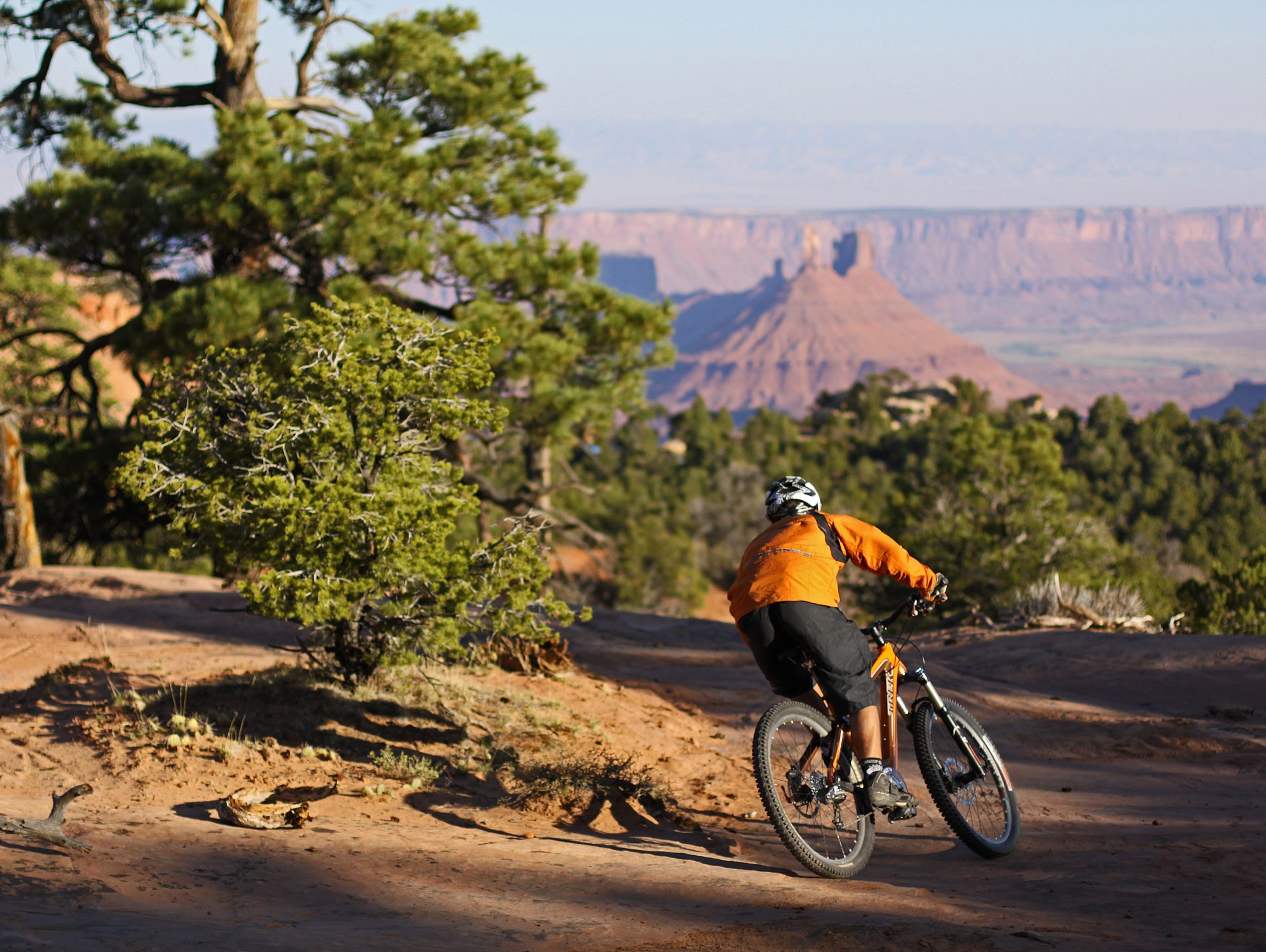 Mountain biker leans into a fast turn on the downhill slickrock section of the Porcupine Rim Trail, part of The Whole Enchilada