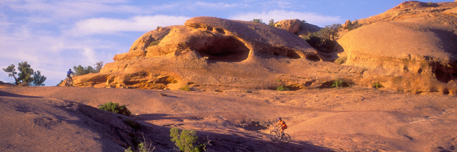 Mountain bikers climb a steep section of the Slickrock Trail during a sunset guided tour close to Moab, UT