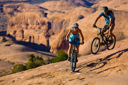 A couple traverses a slickrock fin on a guided tour of the classic Slickrock Trail at Moab UT