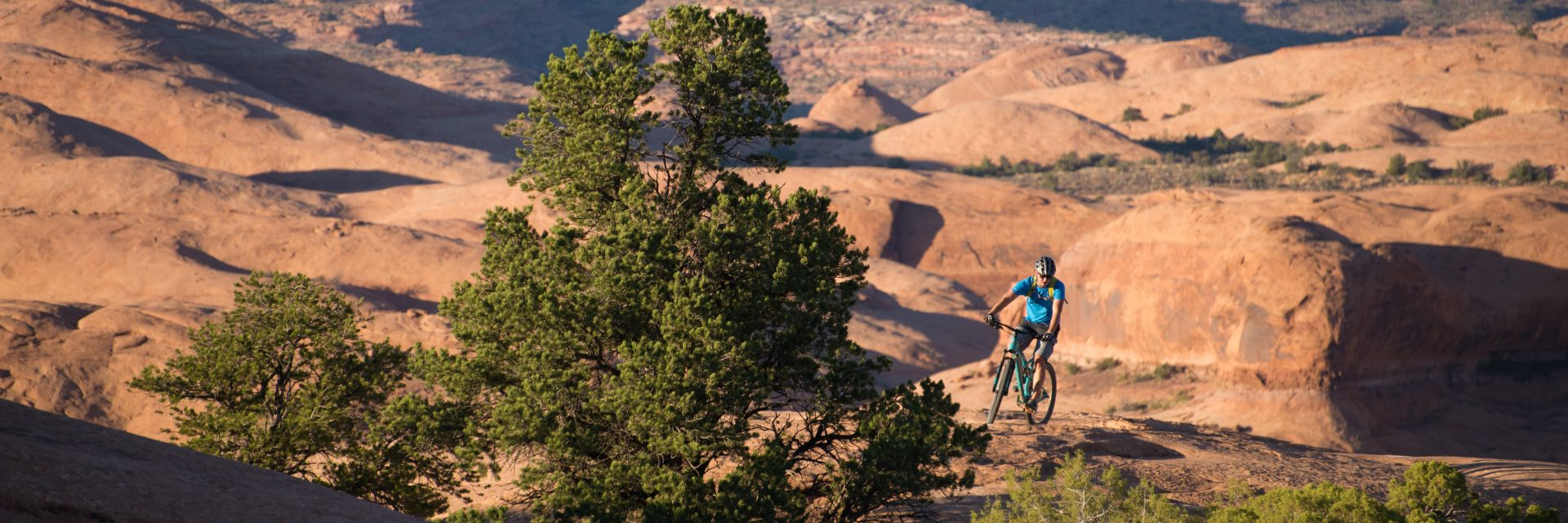 A rider finishes The Practice Loop section of The Slickrock Bike Trail near Moab, UT as the sun sets over Canyonlands National Park