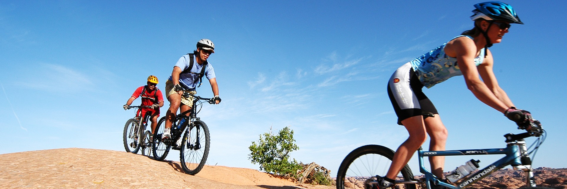 Three riders drop off a tall fin on a guided tour of the Slickrock Trail in Moab, UT