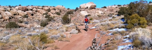 A mountain bike rider passes patches of snow during a winter guided tour on The Sovereign Trail north of Moab, UT