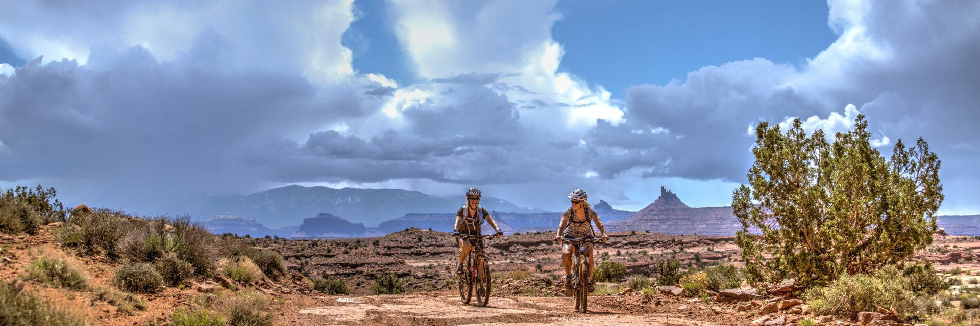 Two riders enjoy an early spring guided mountain bike tour on the Lockhart Basin Road from the Needles to Moab as thunderheads build over the Abajo Mountains in the distance.