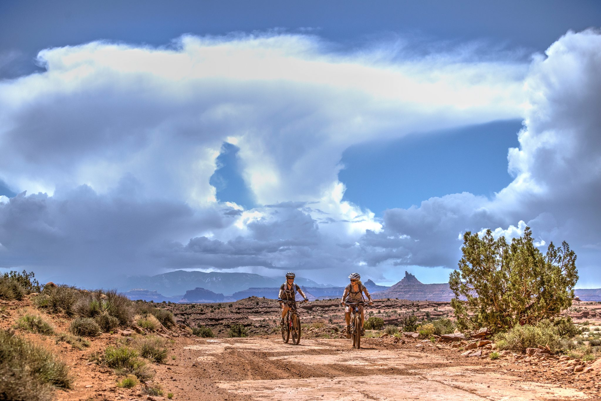 Two riders on The Needles to Moab guided mountain bike tour travel the Lockhart Basin Road away from storms over the Abajo Mountains