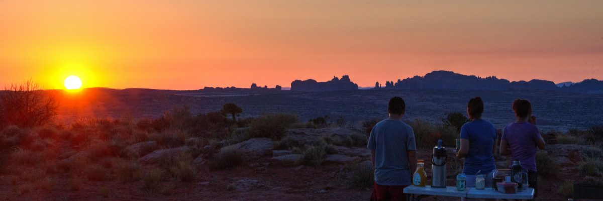 A family enjoys the sun rising above Arches National Park durning Desert Sunrise Mountain Bike Tour