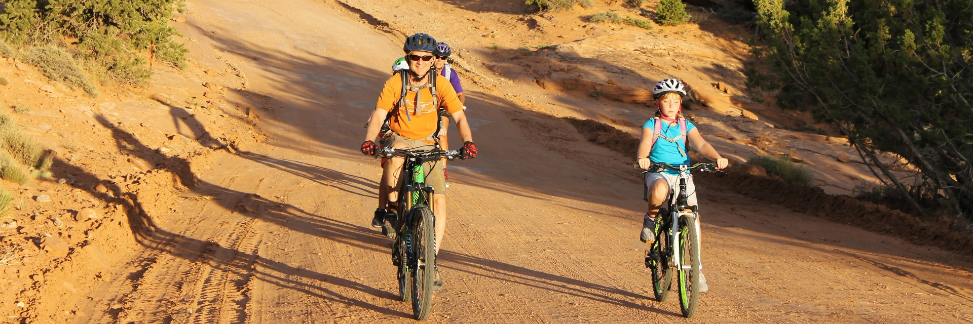 A guide leads kids down the Sand Flats Road on the Sunrise Downhill tour with the early morning sun shining