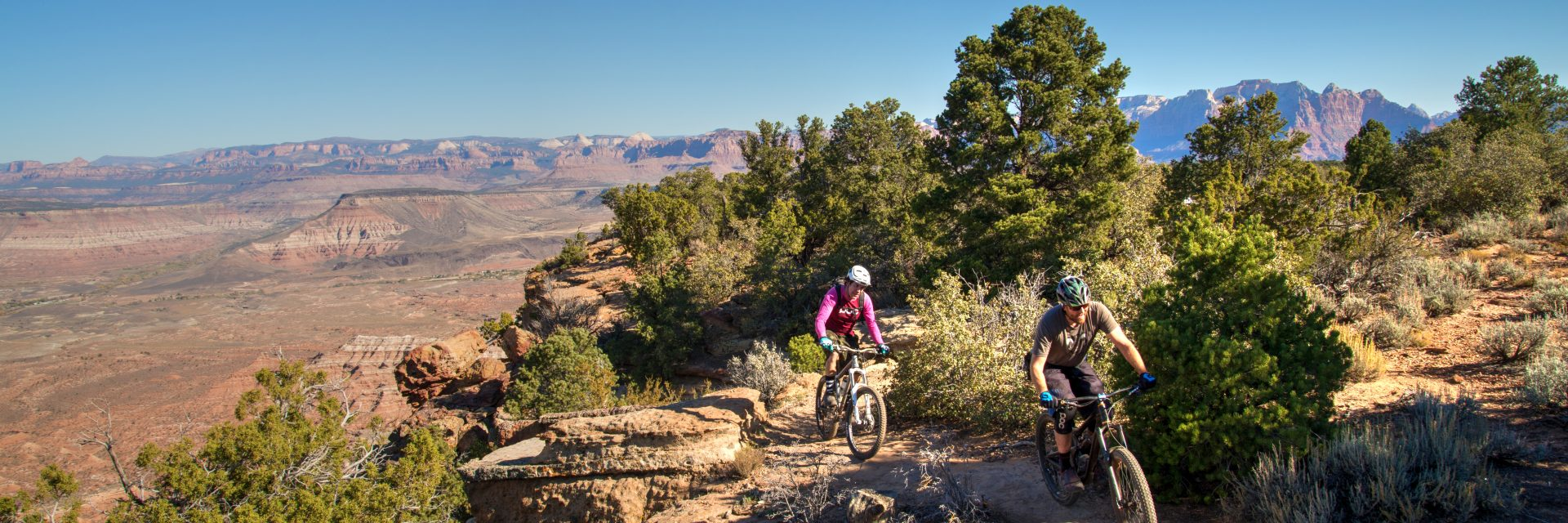 Riders skirt the edge of Gooseberry Mesa on Windmill Trail during a guided mountain bike tour