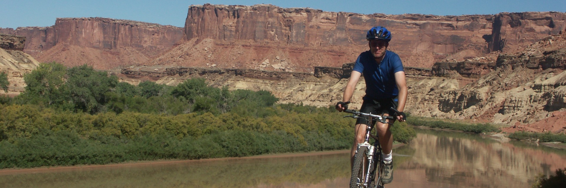 The White Rim Trail two-track road drops down to river level near Potato Bottom where mountain bikers get a close up view