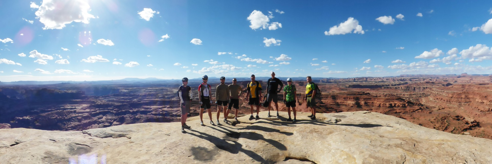 A group of mountain bike riders pose with their guide at White Crack campground on the White Rim Trail guided tour