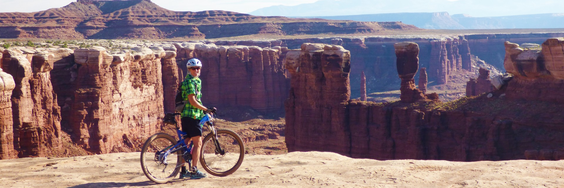 A guest straddles her mountain bike at the edge of the White Rim formation on a guided mountain bike tour