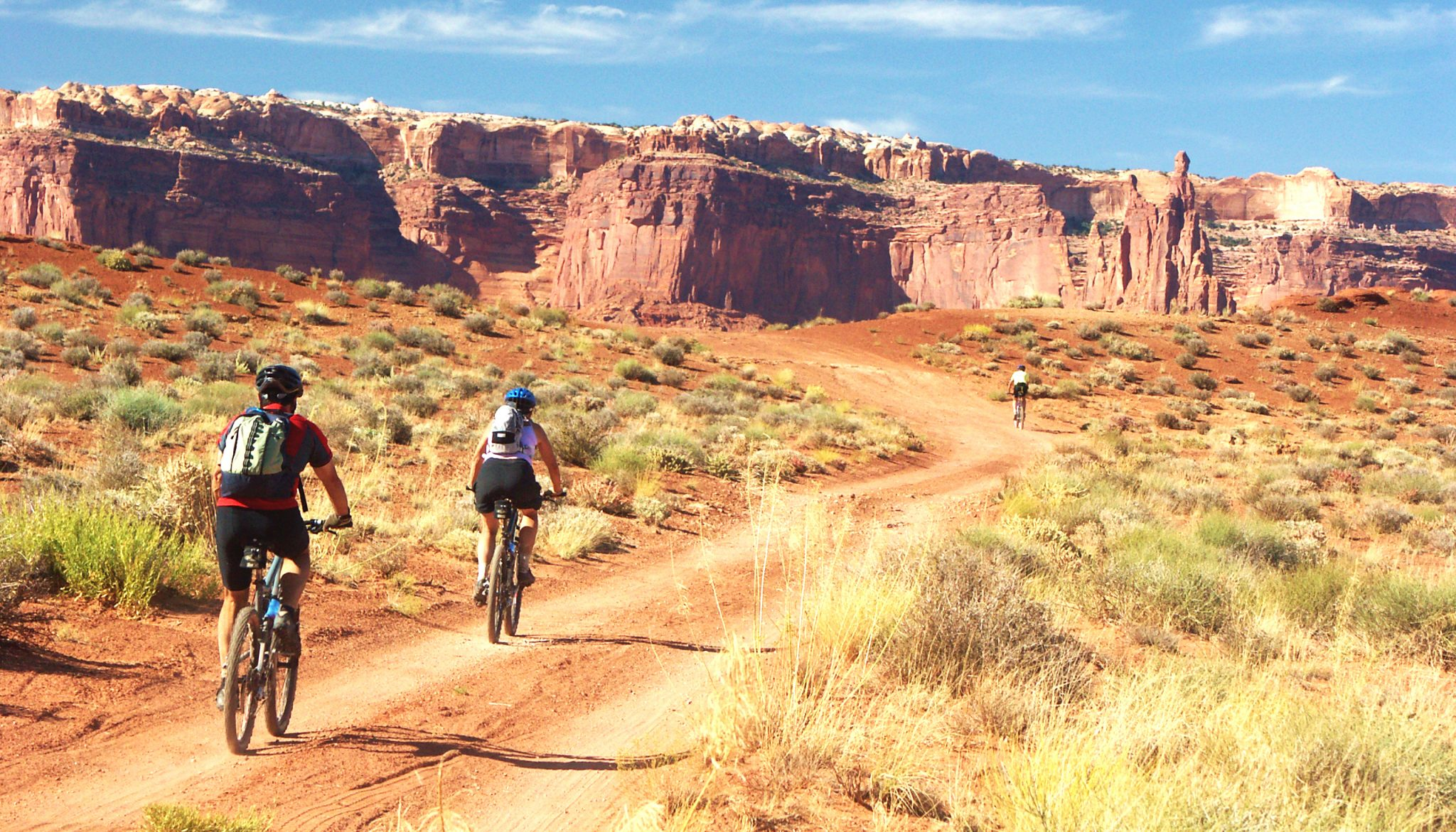 Mountain bikers head toward the Airport Towers on the White Rim Trail in Canyonlands NP