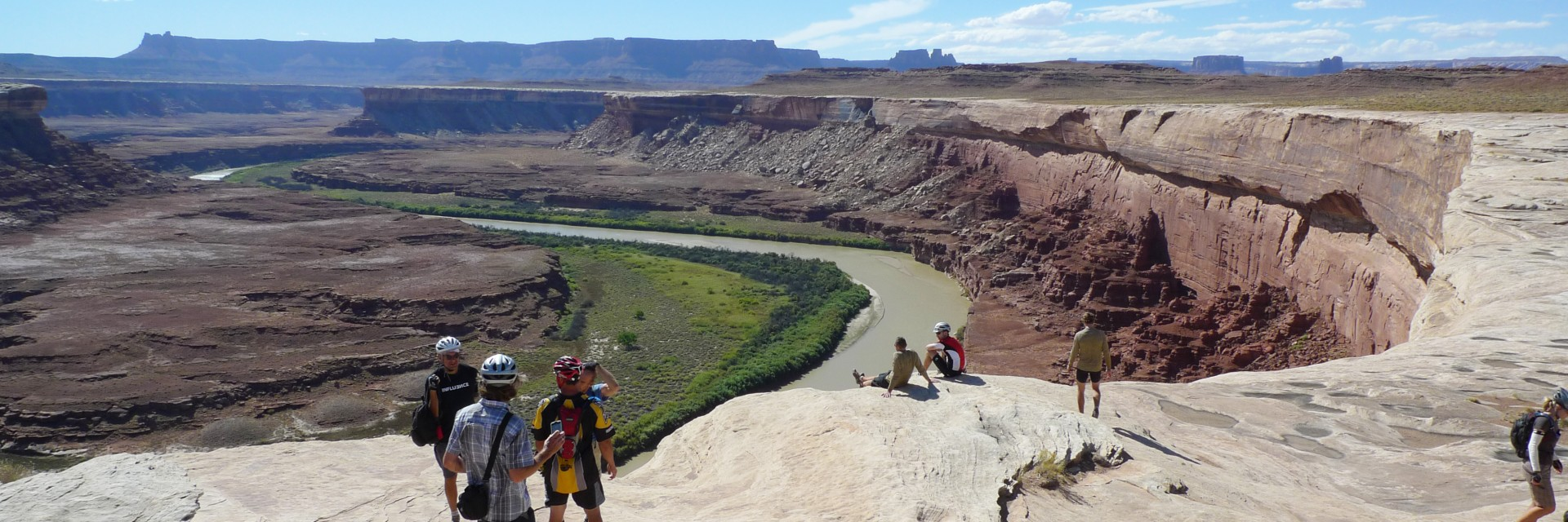 A guide shows mountain bikers the view down onto the Colorado River at Walking Rocks along the White Rim Trail