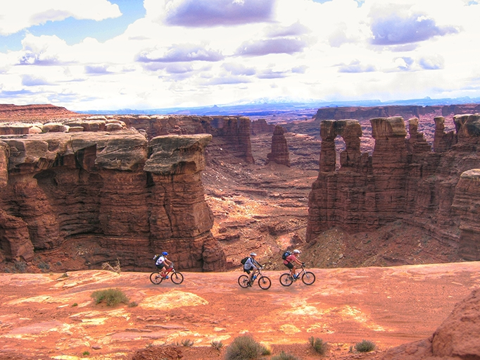 Riders enjoy slickrock along the edge of the White Rim formation on their guided mountain bike tour